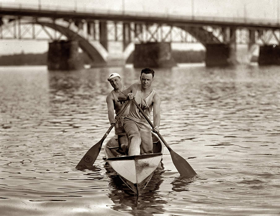 1924. Washington Canoe Club rowers on the Potomac near the recently finished Key Bridge and older Aqueduct Bridge.