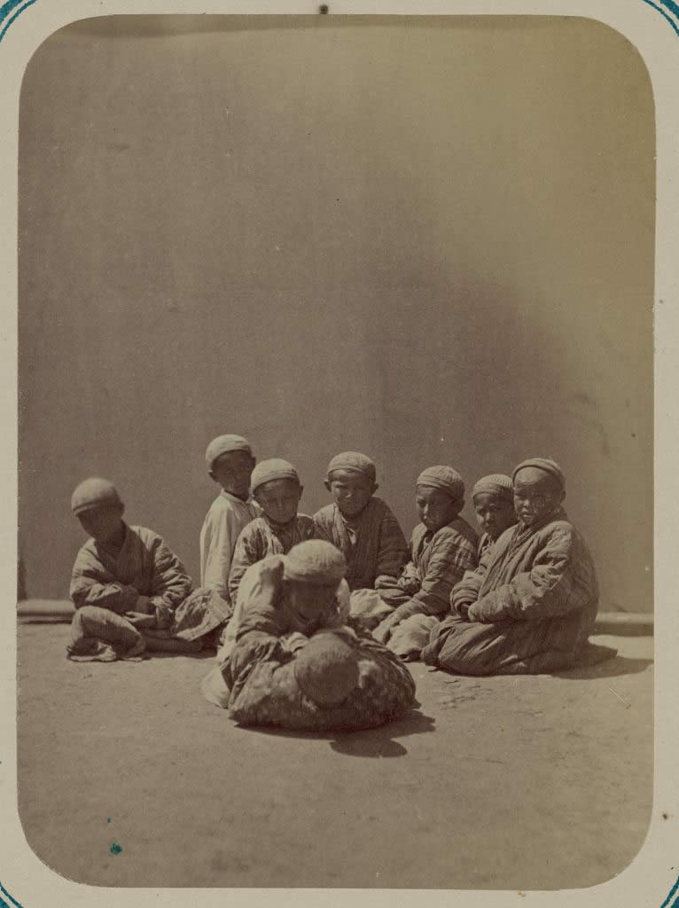 Two young boys wrestling on the ground as others watch. 1865-1872.