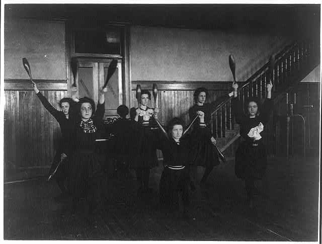 Female students exercising with bowling pins, Western High School.