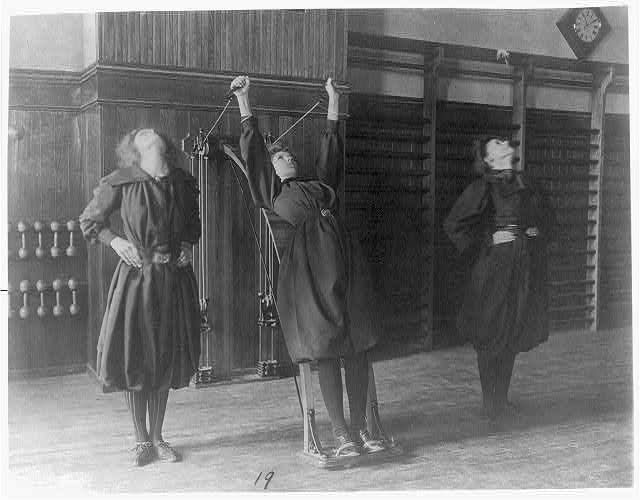 Female students exercising, one with a wall-mounted device using ropes and pulleys, Western High School.