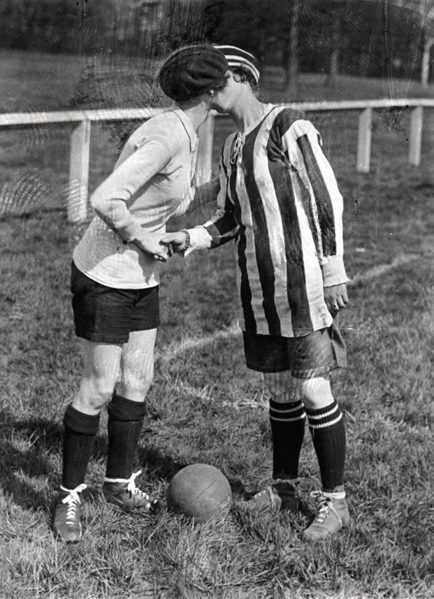 Women's football. The team captains greet each other with a kiss. England, Preston, 1920.