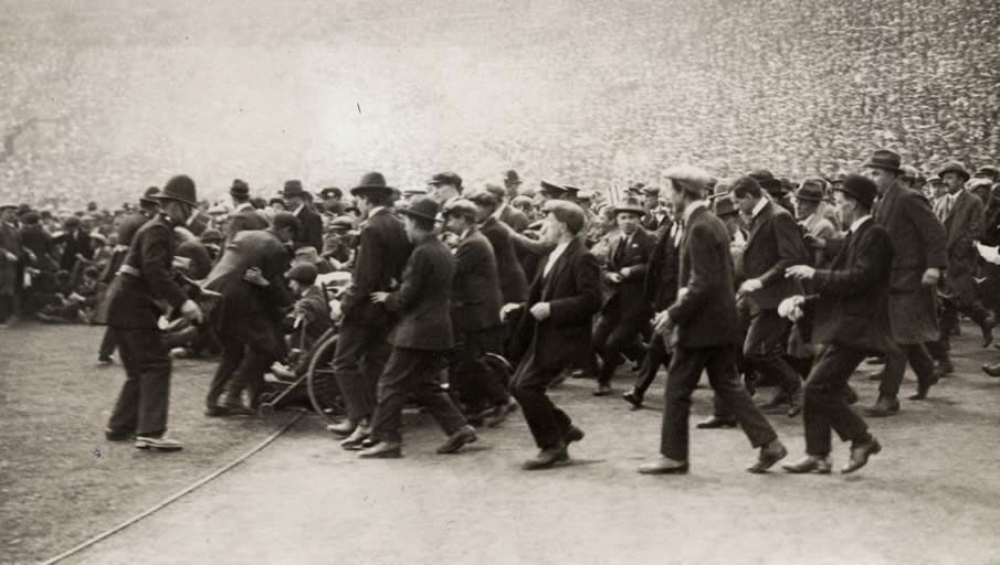 "Supporter ""riots"", the public floods the field, just before the game starts. 300.000 tickets have been sold for the 125.000 seats in the new Wembley stadium. England, London, 1923."