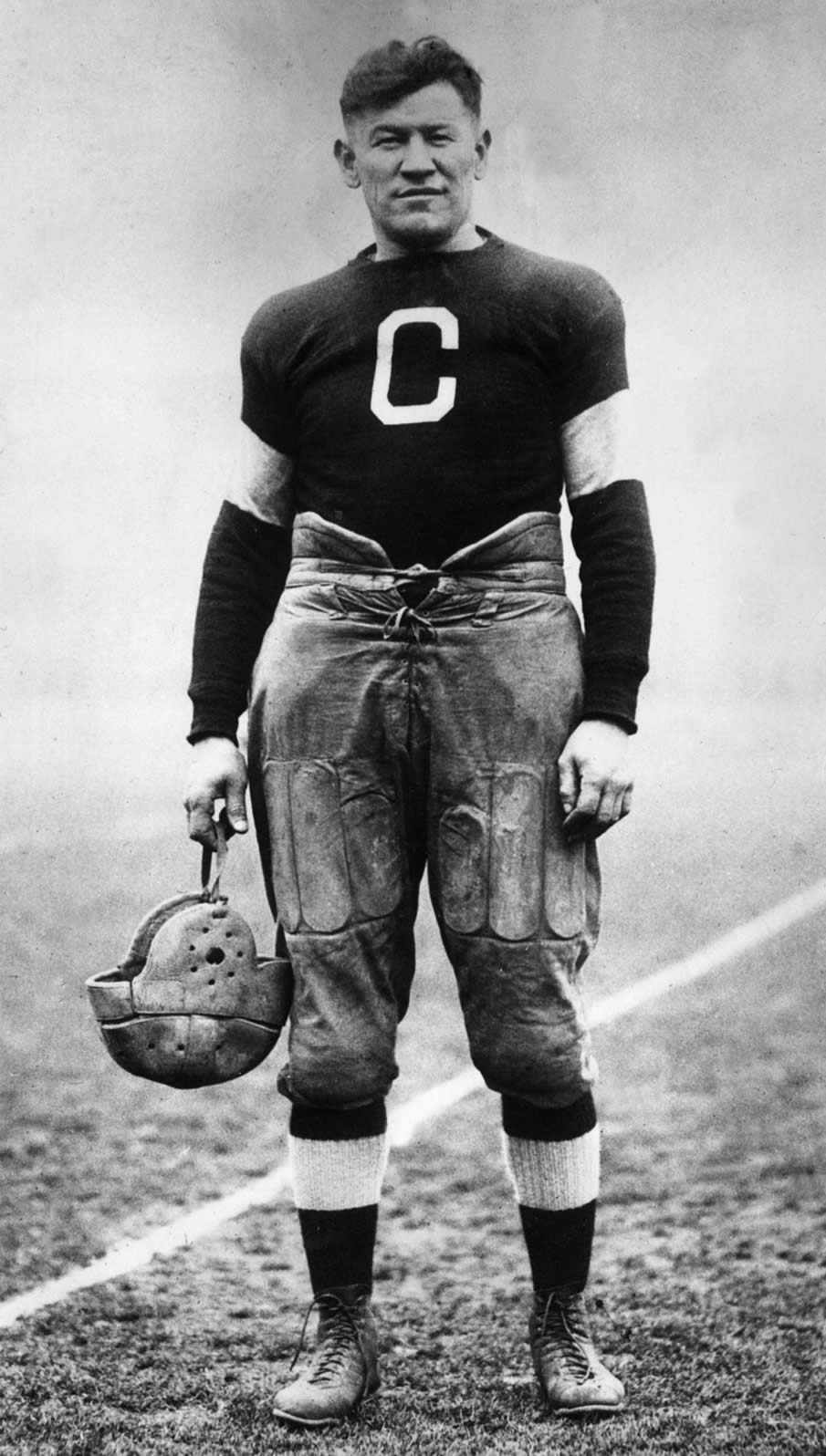circa 1915:  American athlete Jim Thorpe posing in a football uniform on a field.