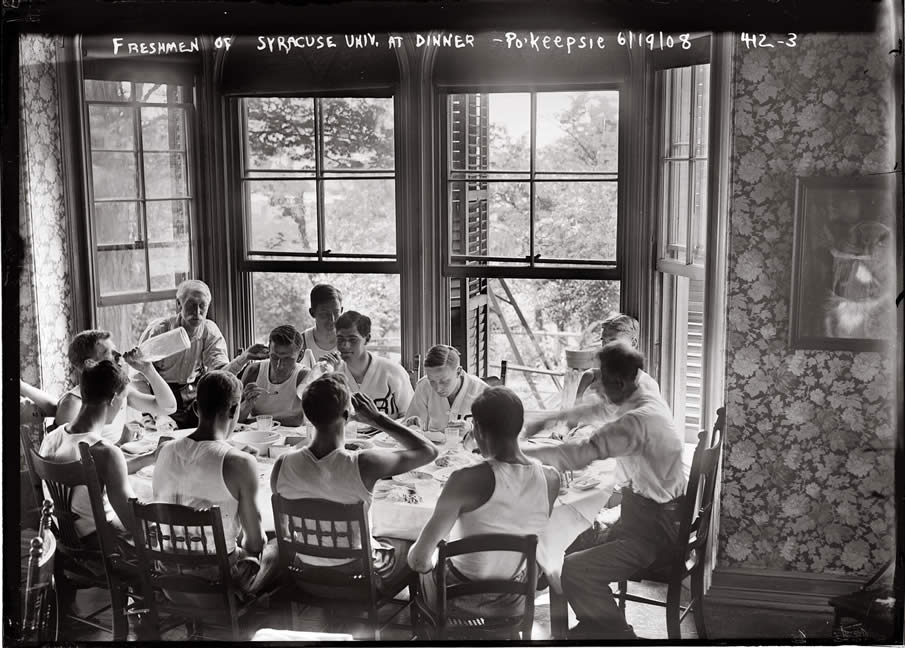 Syracuse freshmen on the rowing team sit around the dinner table on June 19, 1908.