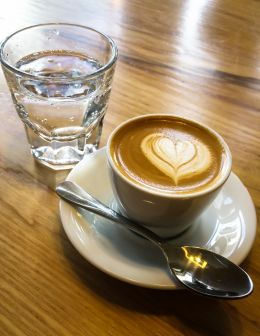 A traditional macchiato served with sparkling water