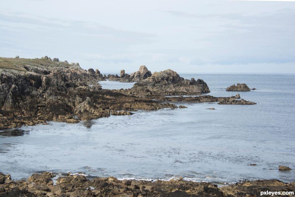 Fierce shore embracing steel blue sea